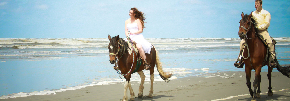 Married couple riding horses on the beach