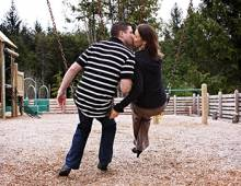Couples pause for a kiss on the swings at Seabrook