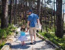 A father with his daughter walking down to the beach