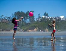 Girls playing with a ball on the beach with Seabrook homes in the background